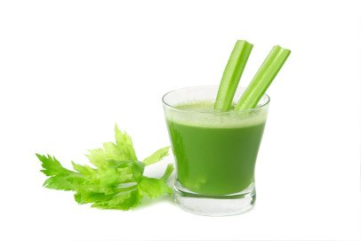 Glass of fresh celery juice with two celery stalks and celery leaves on a white background by Thyroid Nutrition Educators